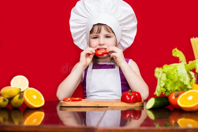 A menina feliz no uniforme do cozinheiro chefe corta vegetais na cozinha Cozinheiro chefe da criança vegetariano fotografia de stock