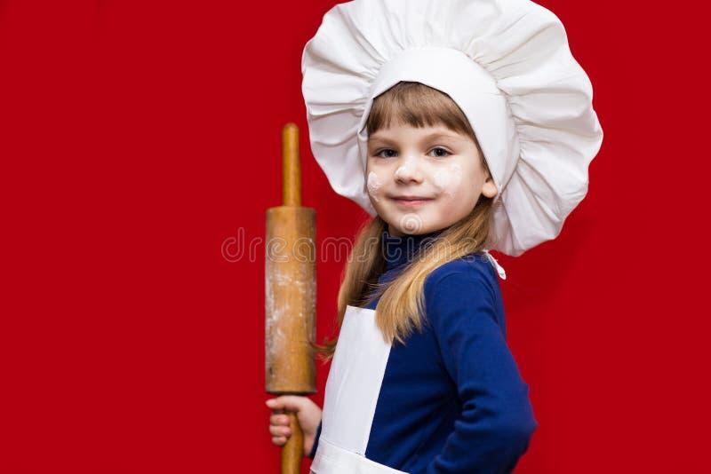 A menina feliz no uniforme do cozinheiro chefe guarda o pino do rolo no vermelho Cozinheiro chefe da criança Cozinhando o conceit foto de stock