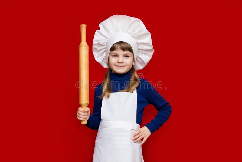 A menina feliz no uniforme do cozinheiro chefe mantém o pino do rolo isolado no vermelho fotografia de stock royalty free