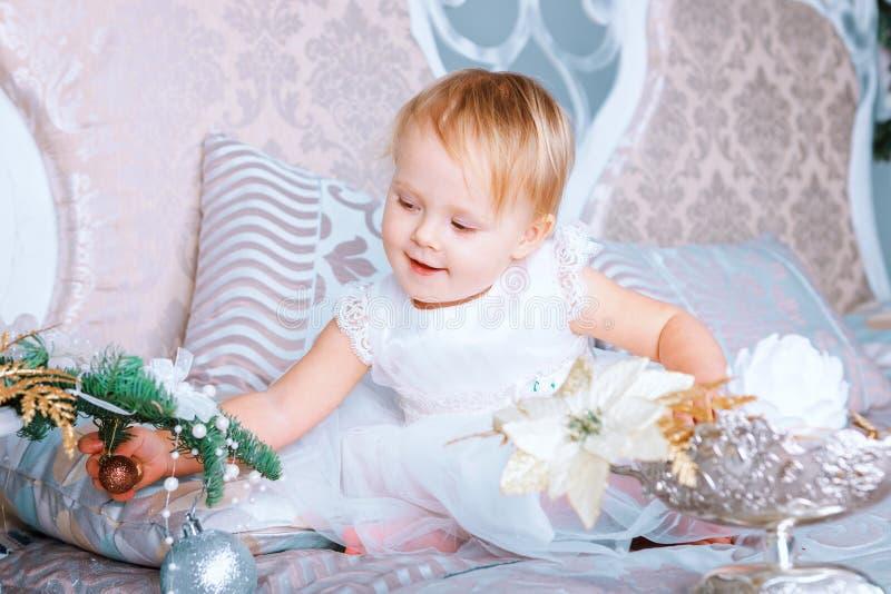 A menina feliz no vestido branco decora a árvore na sala decorada Natal fotos de stock