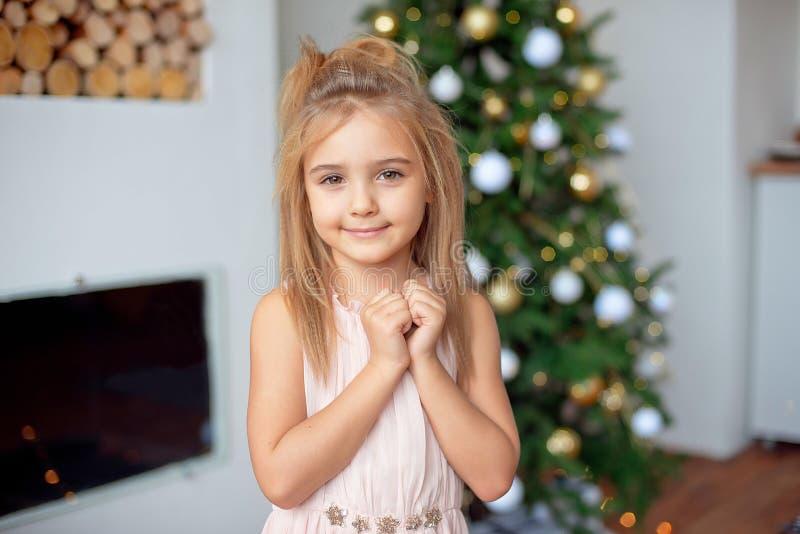 A menina feliz no vestido luxuoso guarda as mãos perto da cara Com luzes e a árvore de Natal coloridas no fundo feriados imagem de stock royalty free