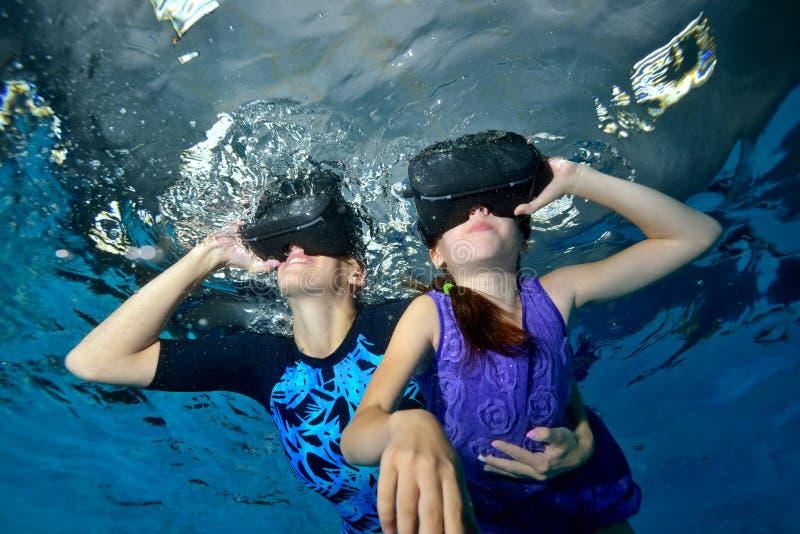 A menina feliz no vestido roxo e a mamã estão nadando em vidros da realidade virtual no underwater principal na associação no fun foto de stock