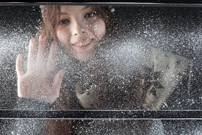 Menina feliz nova atrás do indicador da neve foto de stock
