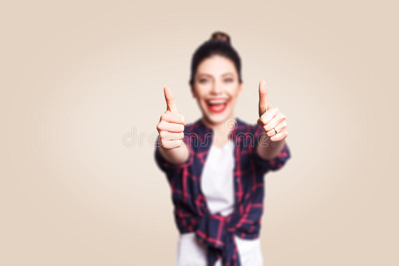 A menina feliz nova com cabelo do estilo ocasional e do bolo manuseia acima de seu dedo, na parede vazia bege com o espaço da cóp foto de stock royalty free