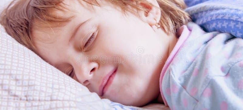 Menina feliz nova da criança das horas de dormir que encontra-se na cama e no sorriso foto de stock royalty free