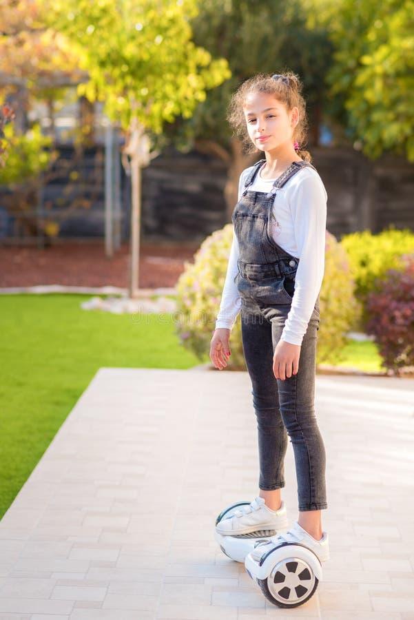Menina feliz nova do adolescente que equilibra no hoverboard elétrico no parque ensolarado, dia ensolarado Vista lateral imagens de stock royalty free