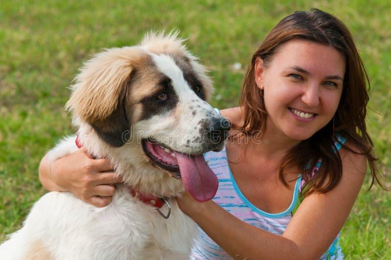 Menina feliz nova que abraça seu cão fotografia de stock royalty free
