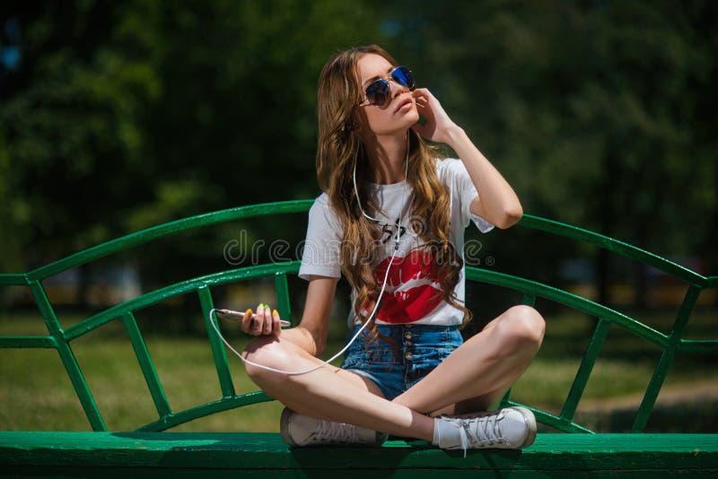 Menina feliz nova que escuta a música nos fones de ouvido com um smartphone foto de stock