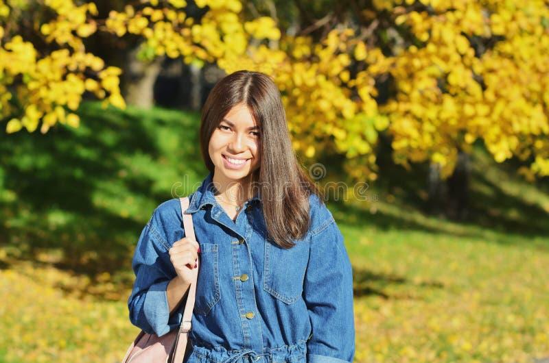 A menina feliz nova que veste um revestimento da sarja de Nimes anda através do parque do outono foto de stock
