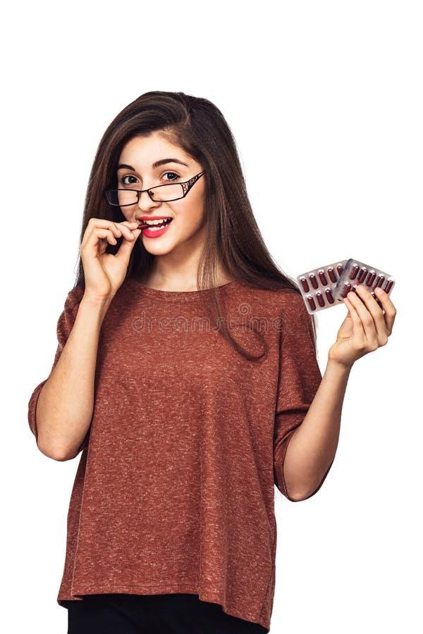 A menina feliz nova realiza em suas mãos e em suas cápsulas dos dentes da medicamentação em um bloco de bolha foto de stock
