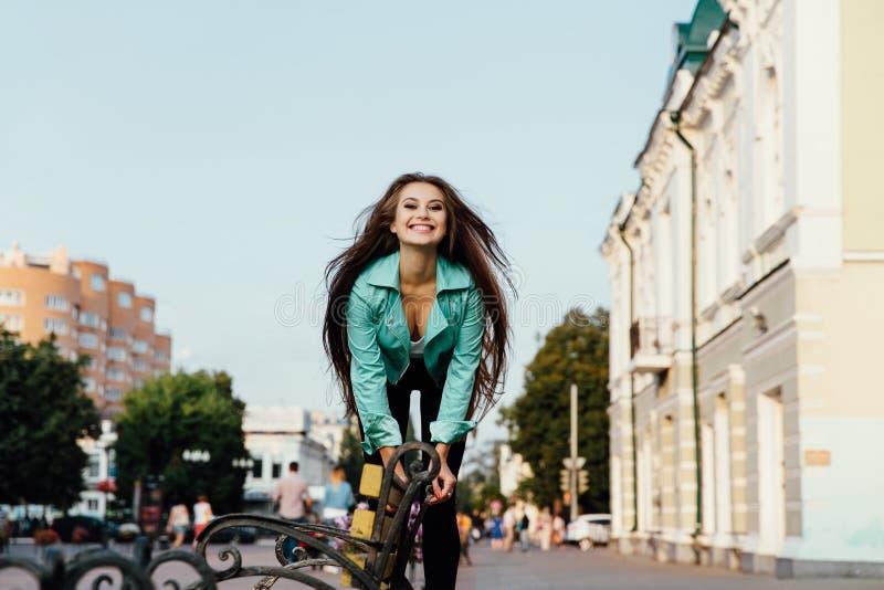 A menina feliz nova, tendo o divertimento, saltos e tem o divertimento na rua lifestyle imagem de stock
