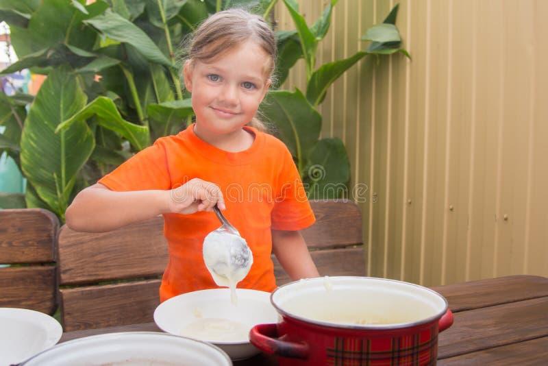 A menina feliz põe o cereal em uma bacia imagens de stock