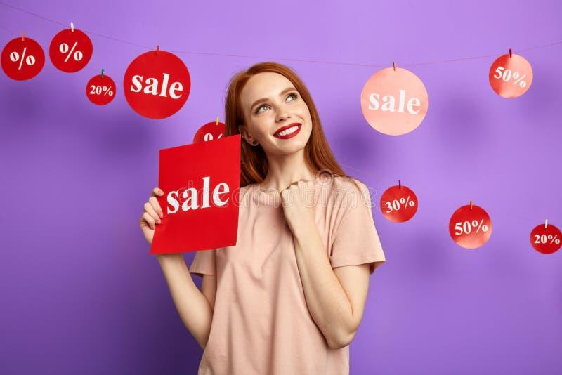 Menina feliz pensativa pensativa com um sinal da venda que olha acima foto de stock royalty free