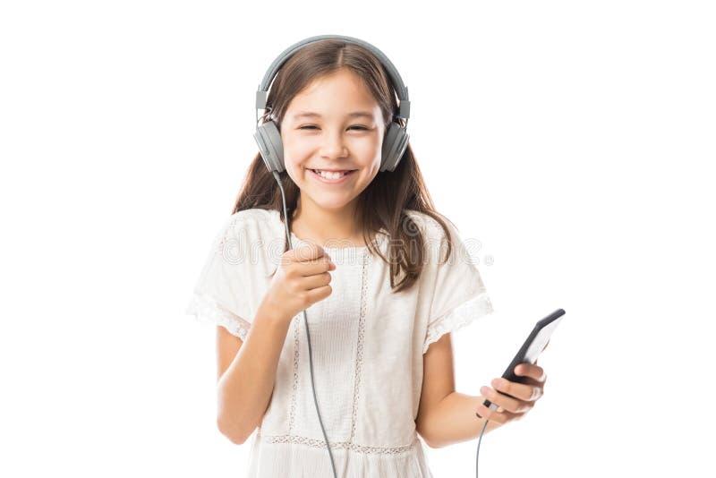 Menina feliz pequena com os fones de ouvido que têm o divertimento que escuta a MU imagens de stock royalty free
