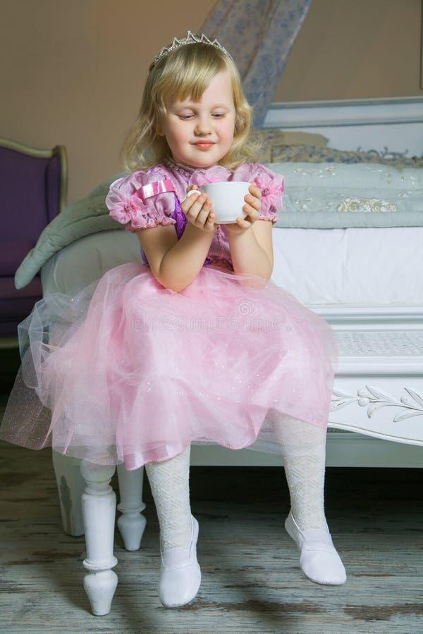 Menina feliz pequena da princesa no vestido e na coroa cor-de-rosa em sua sala real que senta-se na cadeira e que guarda o copo d fotos de stock
