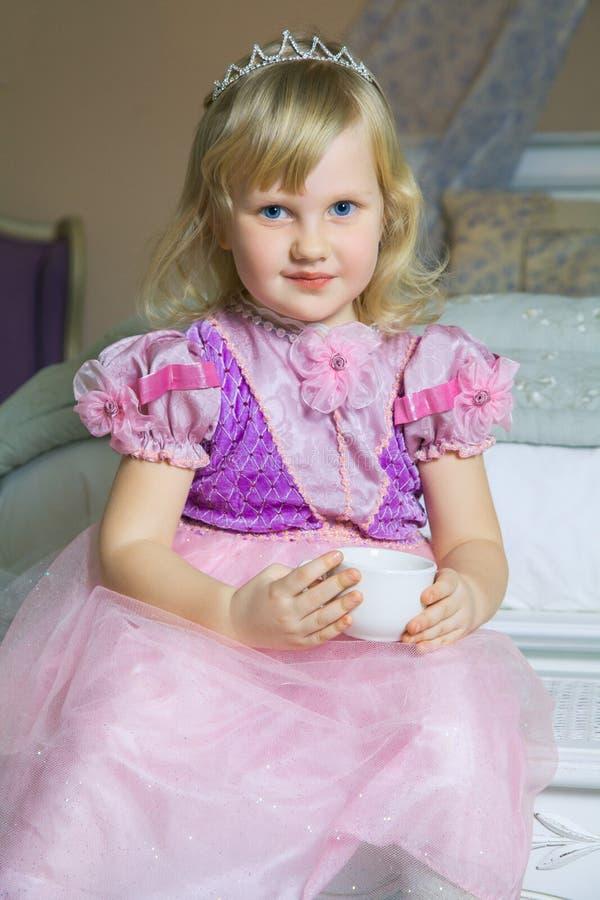 Menina feliz pequena da princesa no vestido e na coroa cor-de-rosa em sua sala real que senta-se na cadeira e que guarda o copo d imagem de stock