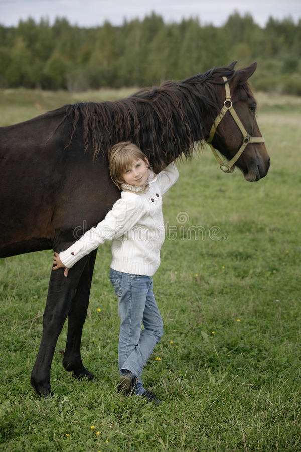 Menina feliz pequena em uma camiseta branca que está e que abraça o dia morno do outono do cavalo Retrato do estilo de vida imagem de stock