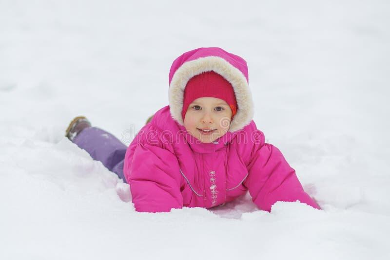 A menina feliz pequena encontra-se na neve imagens de stock royalty free