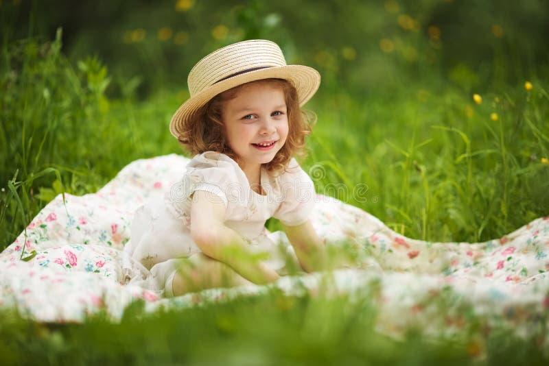 A menina feliz pequena está sentando-se e está descansando-se imagem de stock royalty free