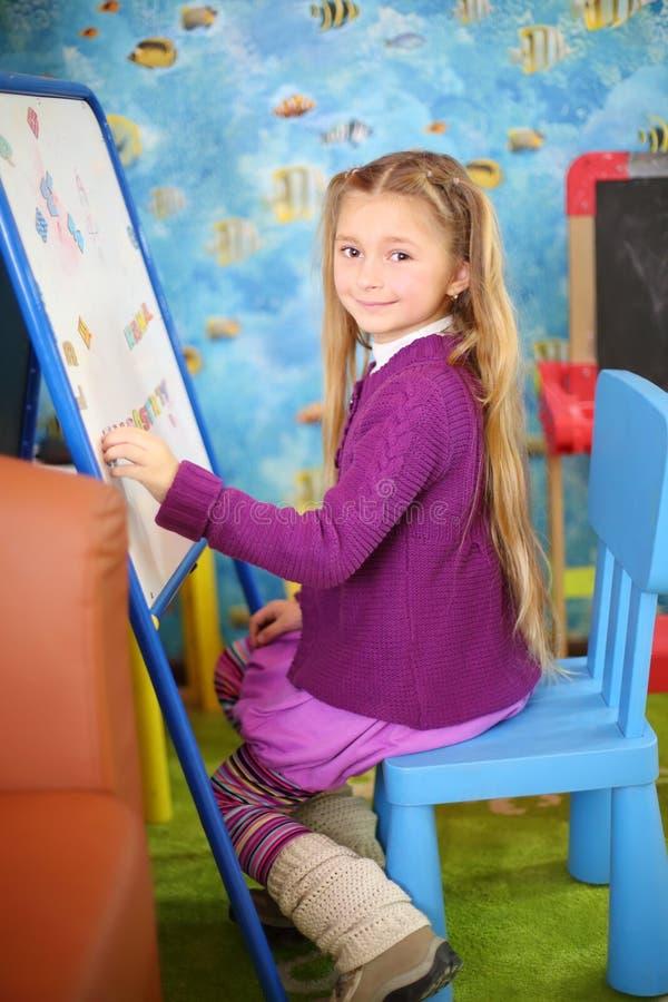 A menina feliz pequena joga com os ímãs na sala de crianças. imagens de stock royalty free