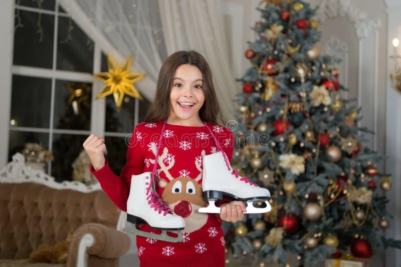 menina feliz pequena no Natal Ano novo feliz A manhã antes do Xmas Menina com patins Atividade do inverno Ano novo fotografia de stock