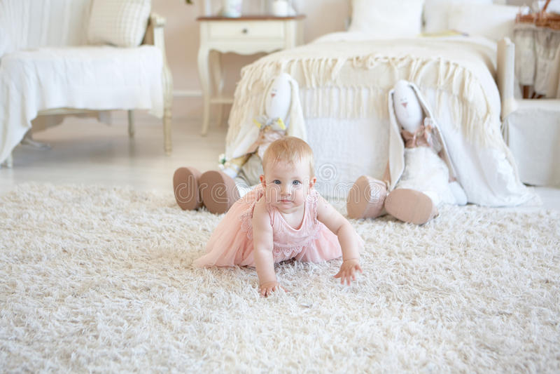 A menina feliz pequena no rastejamento cor-de-rosa do vestido e dois brincam o beh dos coelhos fotografia de stock
