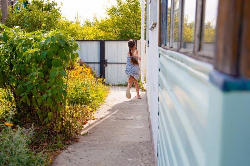 menina feliz pequena que corre ao virar da esquina de uma casa em uma vila do verão imagem de stock royalty free