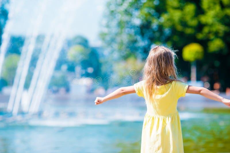 A menina feliz pequena tem o divertimento perto da fonte da rua em imagens de stock royalty free