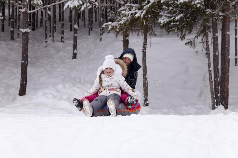A menina feliz prepara-se para deslizar para baixo um monte nevado foto de stock royalty free