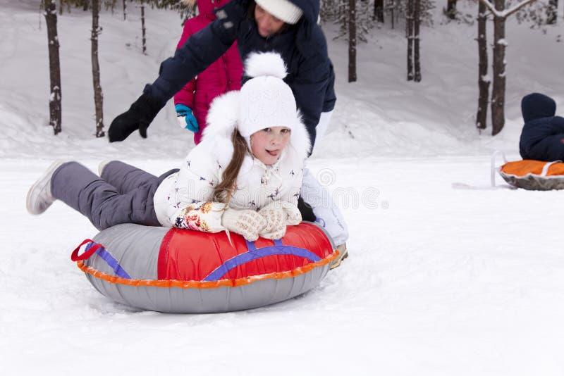 A menina feliz prepara-se para deslizar para baixo um monte nevado imagens de stock royalty free