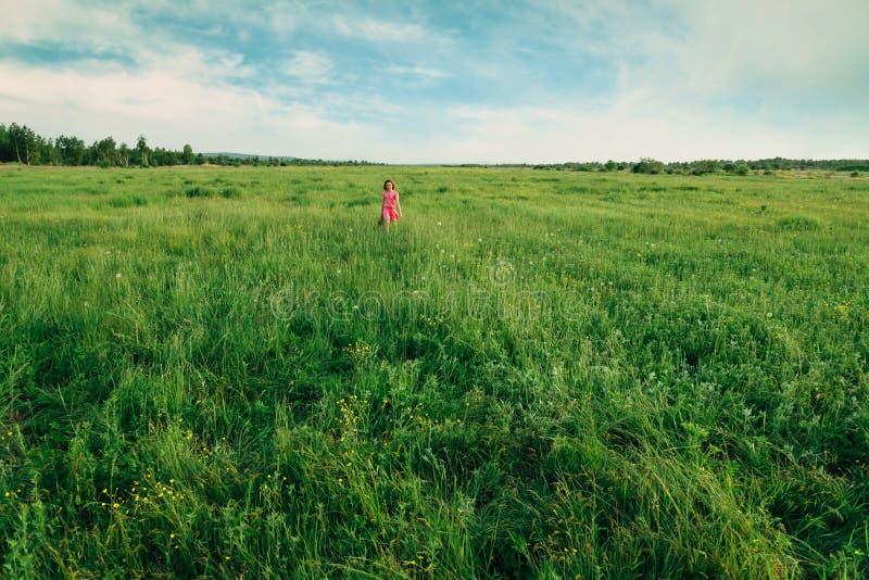 Menina feliz que anda no prado do verão imagem de stock