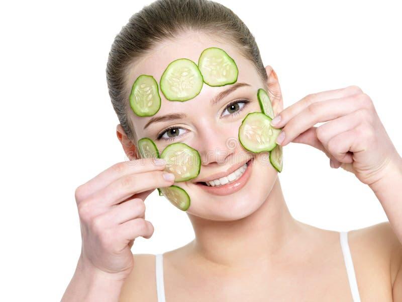 Menina feliz que aplica a máscara facial do pepino imagens de stock royalty free