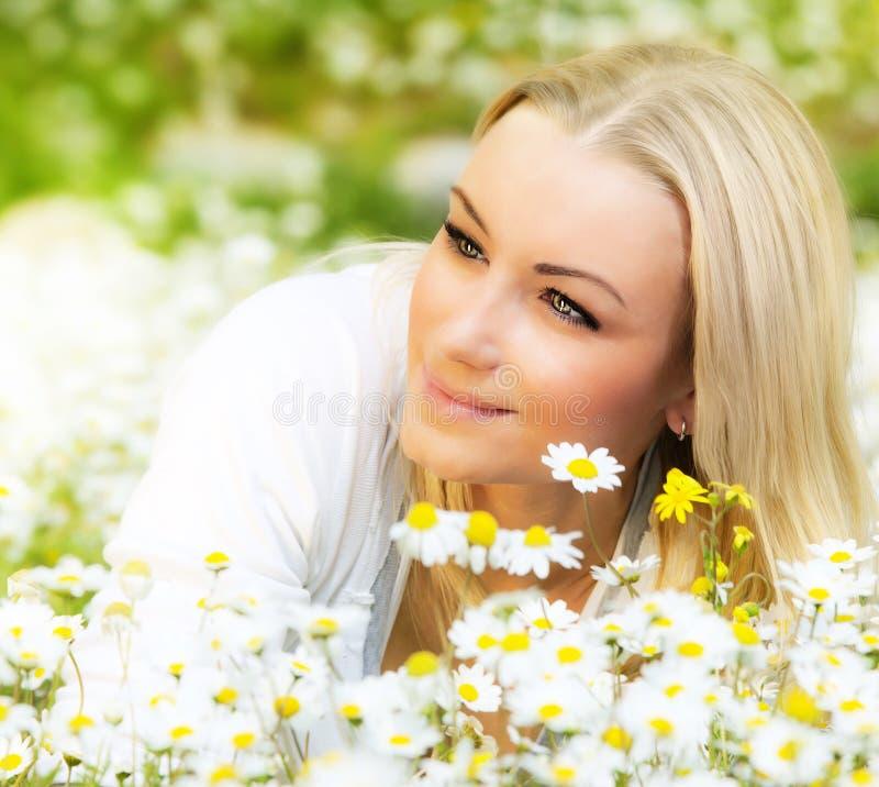 Menina feliz que aprecia o campo de flor da margarida imagem de stock