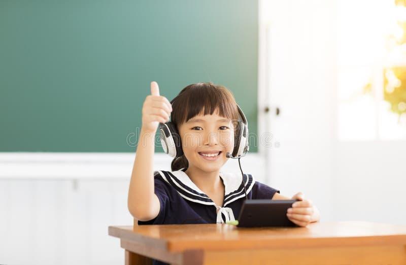 Menina feliz que aprende e que mostra o polegar acima imagem de stock royalty free