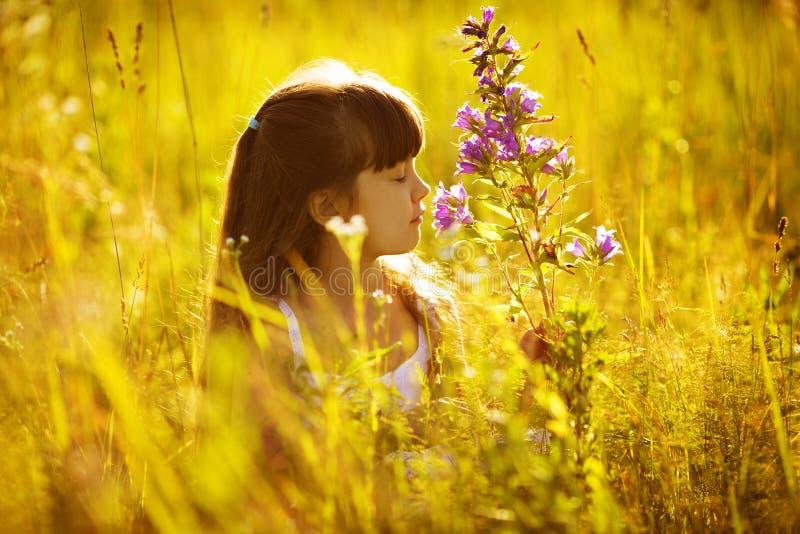 Menina feliz que cheira uma flor imagem de stock