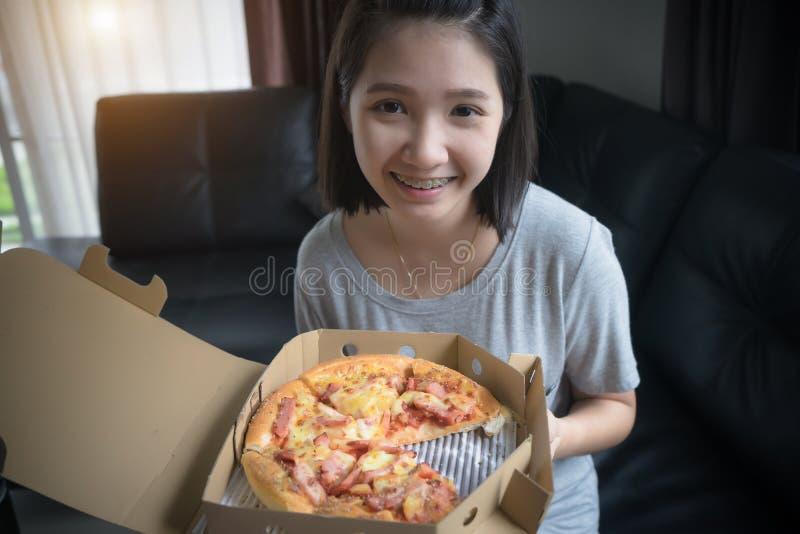 Menina feliz que come a pizza em casa imagens de stock royalty free