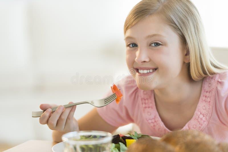 Menina feliz que come a salada na mesa de jantar imagem de stock royalty free