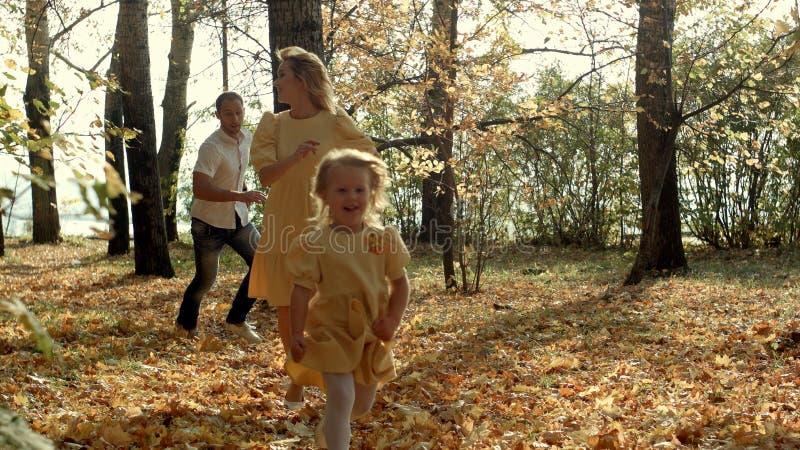 Menina feliz que corre antes de seus pais no parque do outono foto de stock