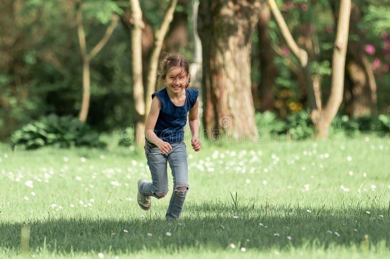 Menina feliz que corre através do prado em um dia de verão foto de stock royalty free