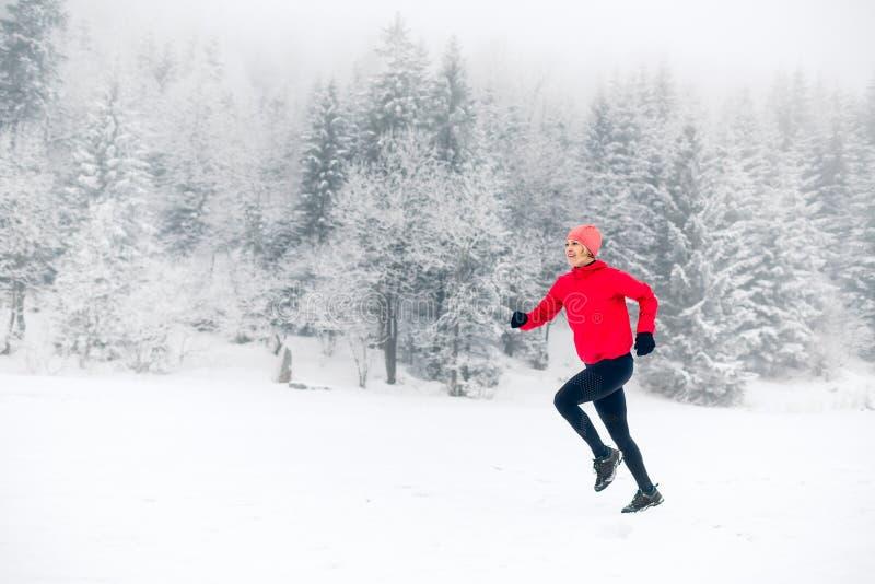 Menina feliz que corre na neve em montanhas do inverno imagens de stock royalty free