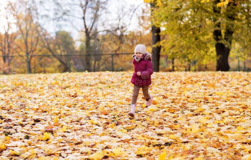 Menina feliz que corre no parque do outono fotos de stock