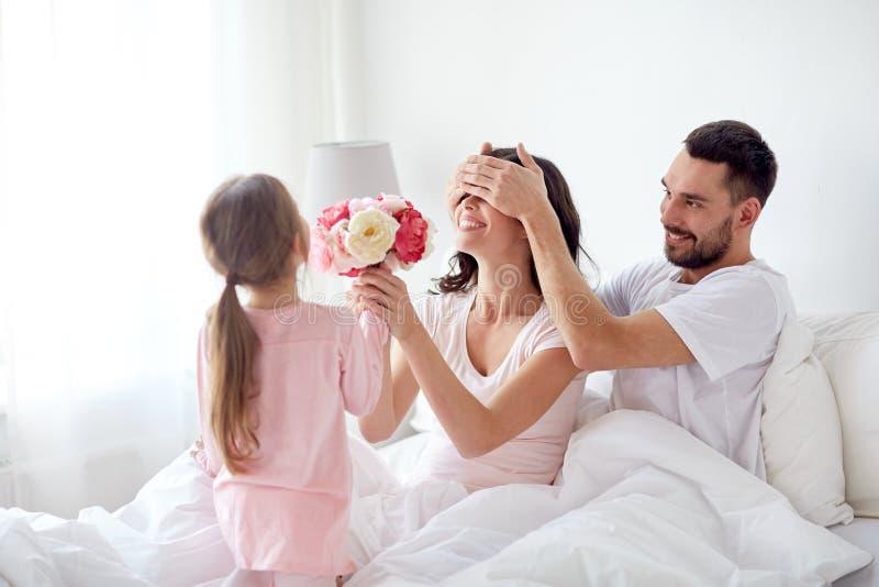 Menina feliz que dá flores à mãe na cama em casa imagem de stock