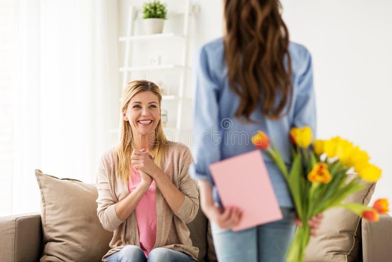 Menina feliz que dá flores para serir de mãe em casa imagens de stock royalty free