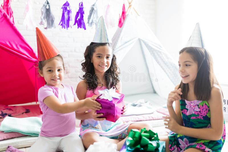 Menina feliz que dá o presente de aniversário ao amigo durante o partido de pijama imagem de stock