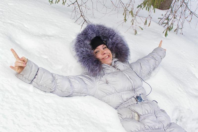 Menina feliz que encontra-se na neve foto de stock