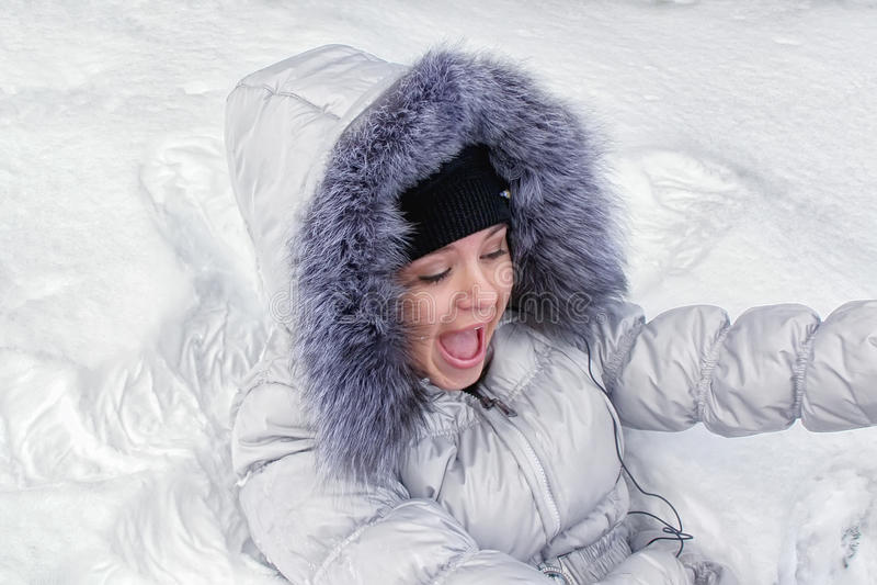 Menina feliz que encontra-se na neve fotografia de stock royalty free