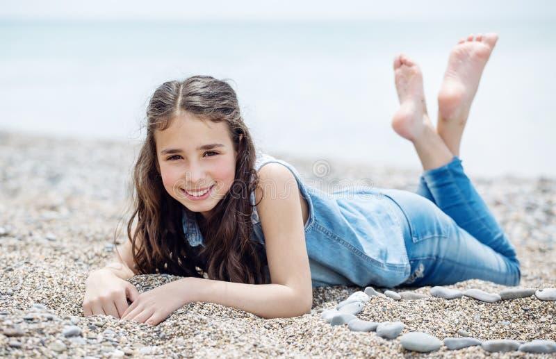 Menina feliz que encontra-se na praia imagem de stock royalty free