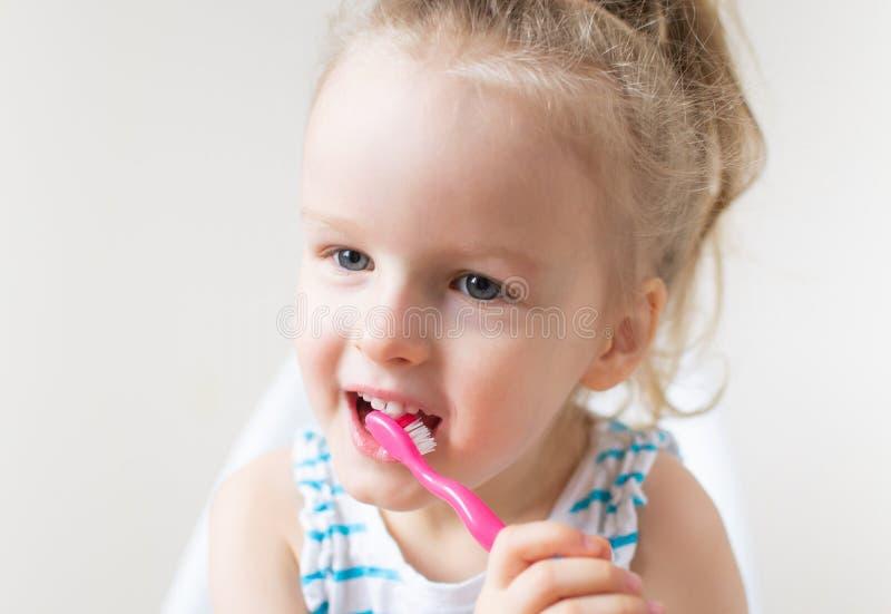 Menina feliz que escova seus dentes, escova de dentes cor-de-rosa, higiene dental, manhã fotos de stock royalty free