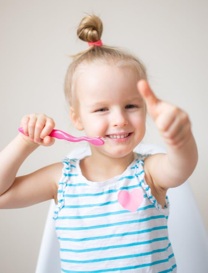 Menina feliz que escova seus dentes, escova de dentes cor-de-rosa, higiene dental, noite da manhã saudável foto de stock