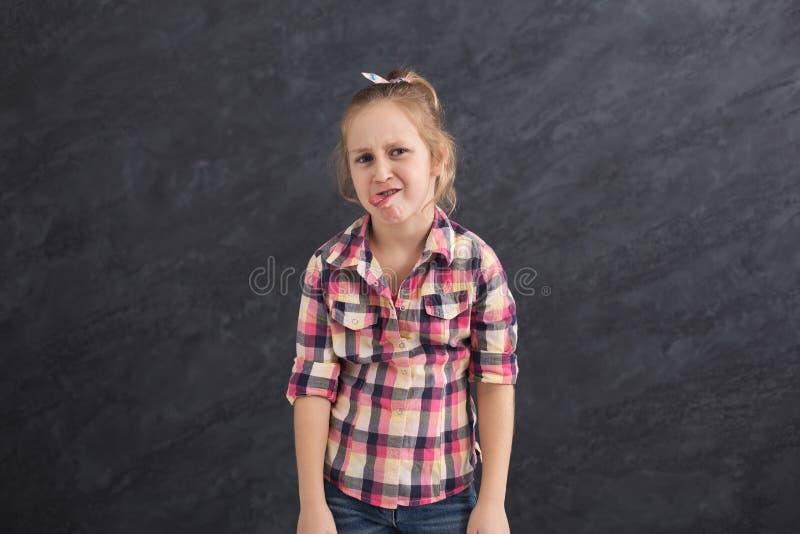 Menina feliz que faz caretas no fundo cinzento foto de stock